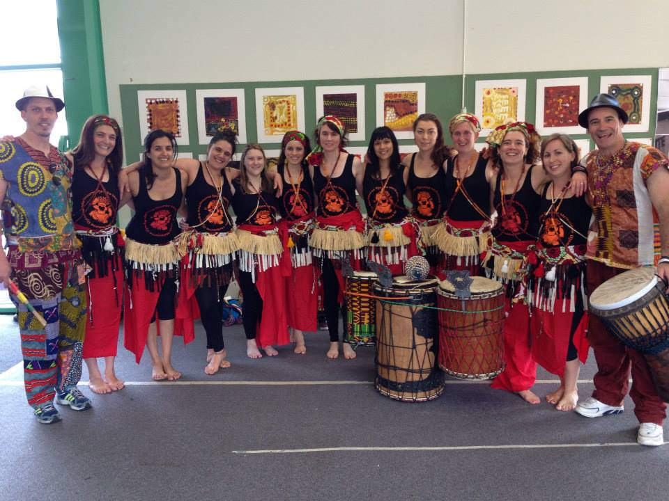 Group of dancers standing in a line with Melbourne Djembe singlets and raffia skirts