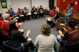 People sitting in a circle playing African drums