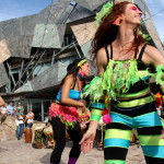 Beautiful dancers in costume in front of interesting building at Federation Square