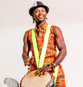 African man smiling, playing djembe