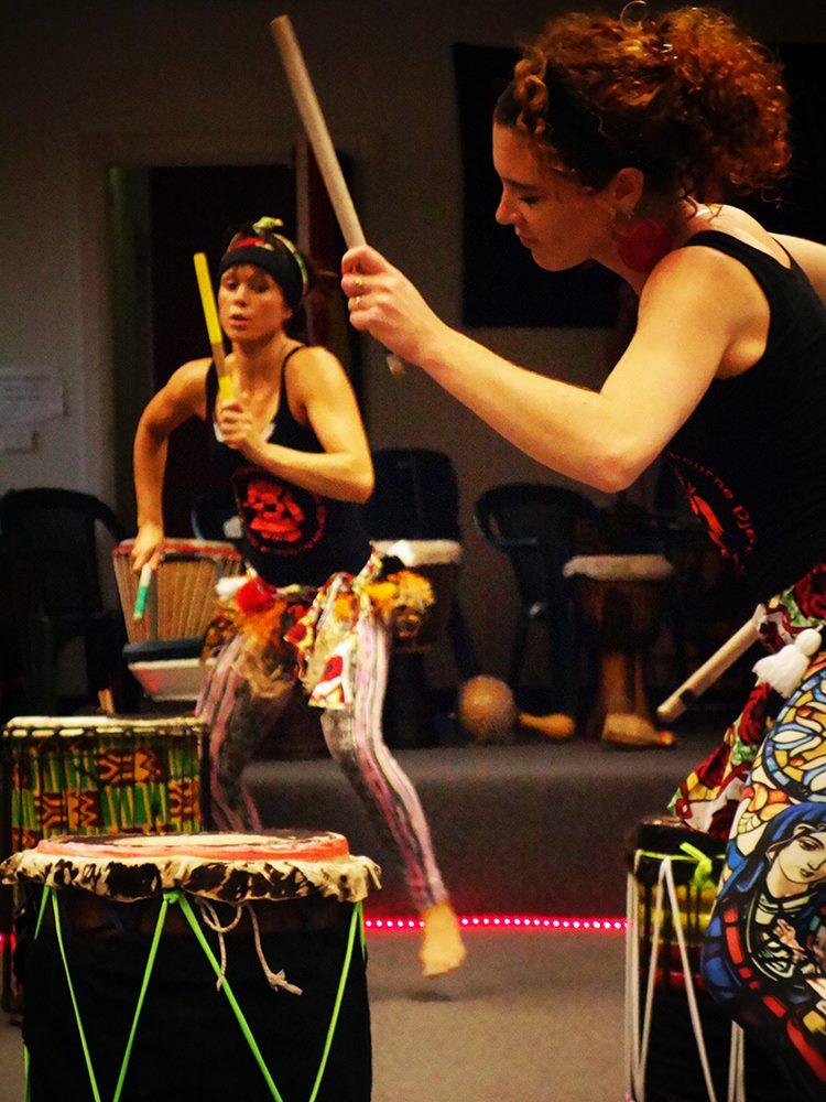 Dancers playing dunduns (stick drums)