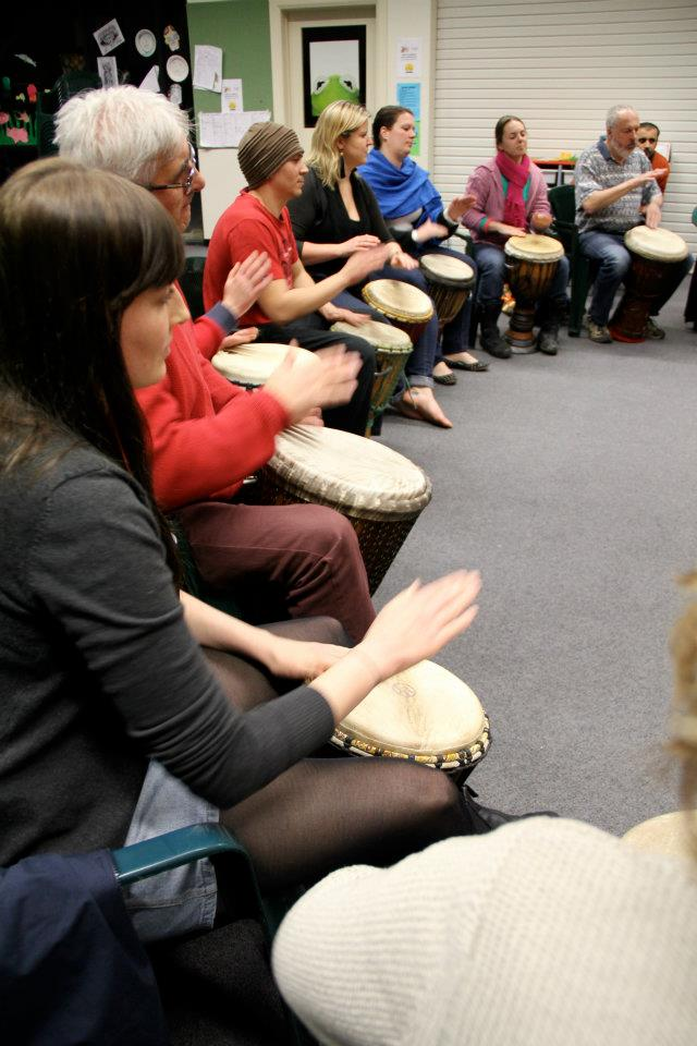 Djembe players sitting in a row