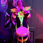 Drumming ensemble with djembes and dunduns, exciting fluro costumes