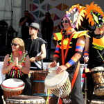 Group of 6 people in costume playing African drums