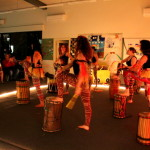 Dancers playing dunduns (African stick drums)